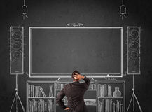 Businessman in front of a home cinema system. Young businessman standing and enjoying home cinema system sketched on a chalkboard royalty free stock images