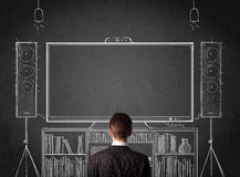 Businessman in front of a home cinema system. Young businessman standing and enjoying home cinema system sketched on a chalkboard stock images