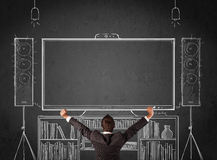 Businessman in front of a home cinema system. Young businessman standing and enjoying home cinema system sketched on a chalkboard royalty free stock photo