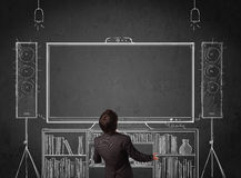 Businessman in front of a home cinema system. Young businessman standing and enjoying home cinema system sketched on a chalkboard stock photography