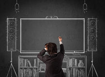 Businessman in front of a home cinema system. Young businessman standing and enjoying home cinema system sketched on a chalkboard Royalty Free Stock Photos