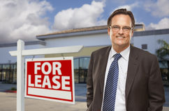 Businessman In Front of Office Building and For Lease Sign. Handsome Businessman In Front of Vacant Office Building and For Lease Real Estate Sign Stock Photo