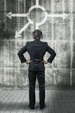 Businessman in front of a wall with different direction arrows. Metaphoric for difficult decisions Royalty Free Stock Images
