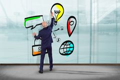 Businessman in front of a wall with a Hand drawn icon of busine. View of a Businessman in front of a wall with a Hand drawn icon of business, multimedia and Stock Photo