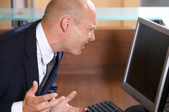Businessman frowning in front of computer monitor Stock Image