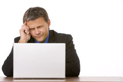 Businessman Frowning While Looking At Laptop Royalty Free Stock Images