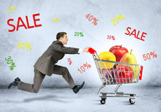 Businessman with fruits in shopping cart. On grey background Royalty Free Stock Photos