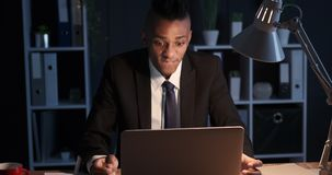 Businessman frustrated by online problem at night office. African american businessman getting angry while receiving bad news on laptop at night office stock footage