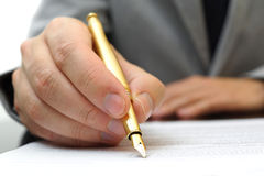Businessman is fulfilling and signing contract with fountain pen Stock Photo