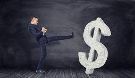 Businessman in full growth kicks off huge concrete dollar sign. Businessman in full growth kicks off a huge concrete dollar sign on a black background. Refusal Stock Photos