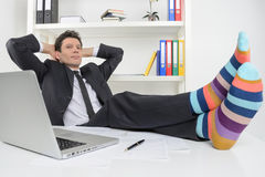 Businessman in funky socks. Confident businessman holding his le Royalty Free Stock Images