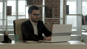 Businessman in funny glasses typing on keyboard stock video