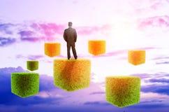 Businessman on futuristic background sky. Businessman standing on futuristic background sky grass cubes Stock Photo