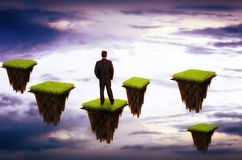 Businessman on futuristic background sky. Businessman standing on futuristic background sky grass earth pieces Royalty Free Stock Images