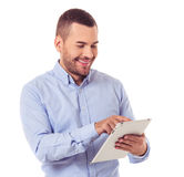 Businessman with gadget. Handsome businessman in smart casual wear is using a digital tablet and smiling, isolated on white Royalty Free Stock Photography