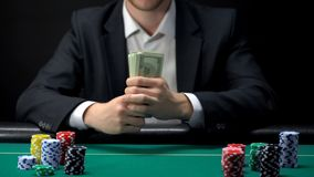 Businessman gambler contemplating betting all money on poker game at casino royalty free stock image
