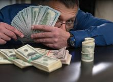 Businessman peering out from a handful of money royalty free stock images