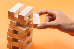 Businessman gambling placing wooden block on a tower Royalty Free Stock Photography