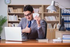 The businessman gambling playing cards at work Stock Photography