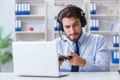 The businessman gamer in office playing games. Businessman gamer in office playing games Stock Photos