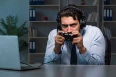 The businessman gamer staying late to play games. Businessman gamer staying late to play games Royalty Free Stock Photos