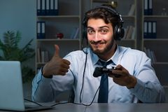 The businessman gamer staying late to play games. Businessman gamer staying late to play games Royalty Free Stock Photo