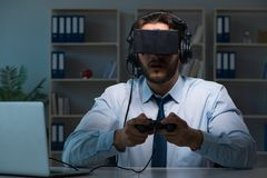 The businessman gamer staying late to play games Royalty Free Stock Photography