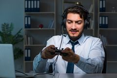 The businessman gamer staying late to play games. Businessman gamer staying late to play games Royalty Free Stock Images