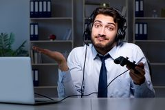 The businessman gamer staying late to play games. Businessman gamer staying late to play games Royalty Free Stock Image