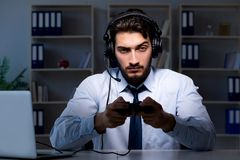 The businessman gamer staying late to play games. Businessman gamer staying late to play games Royalty Free Stock Photography