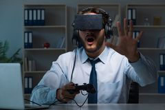The businessman gamer staying late to play games Royalty Free Stock Photo