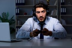 The businessman gamer staying late to play games. Businessman gamer staying late to play games Stock Image