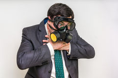 Businessman with gas mask can not breathe bad air. Young businessman with gas mask can not breathe bad air Stock Photos
