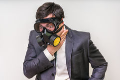 Businessman with gas mask can not breathe bad air. Young businessman with gas mask can not breathe bad air Royalty Free Stock Photography