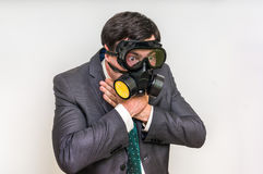 Businessman with gas mask can not breathe bad air. Young businessman with gas mask can not breathe bad air Royalty Free Stock Photos