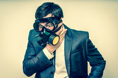 Businessman with gas mask can not breathe bad air. Young businessman with gas mask can not breathe bad air - retro style Royalty Free Stock Photography