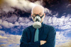 Businessman with gas mask in front of cloudy sky Stock Images