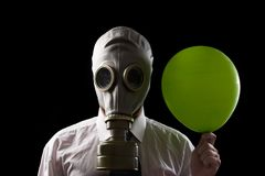 Businessman with gas mask and green baloon. Businessman wearing  gas mask and  holding a green  balloon Royalty Free Stock Photo