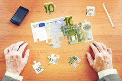 Businessman gathers One hundred Euros as a set of puzzles Royalty Free Stock Photography