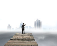 Businessman gazing at city with cloudy under. Businessman gazing at city skyscraper with cloudy under royalty free stock image