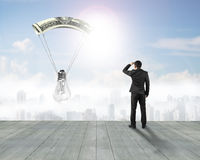 Businessman gazing light bulb with money parachute Royalty Free Stock Photos