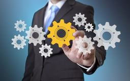 Businessman gears concept. Businessman playing with gears and various cogwheels Stock Images