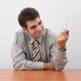 Businessman Generating Ideas. Smiling young businessman holding a light bulb and generating ideas with sitting at the table Royalty Free Stock Photography