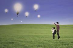 Businessman generation looking at lightbulbs outdoor Stock Image