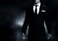 Businessman, gentleman in elegant suit on black background. Middle body view Stock Images