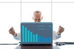 Businessman Gesture Series Graphed - Gratified. Businessman seated in corporate office at desk, clenched fists held outward, gratified with a bar graph showing stock photography