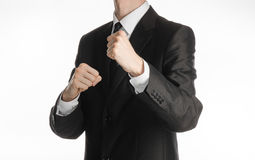 Businessman and gesture topic: a man in a black suit holding his fists in front of him, business struggle. Studio Royalty Free Stock Photo