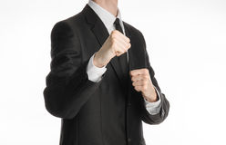 Businessman and gesture topic: a man in a black suit holding his fists in front of him, business struggle. Studio Stock Image