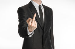 Businessman and gesture topic: a man in a black suit showing middle finger on an isolated white background in studio Stock Photo
