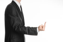Businessman and gesture topic: a man in a black suit showing middle finger on an isolated white background in studio Stock Image